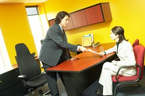 Cheesy picture of a woman interviewing for a job in cheap-looking office